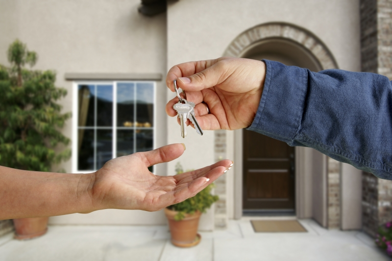 812327-handing-over-the-house-keys-in-front-of-new-home